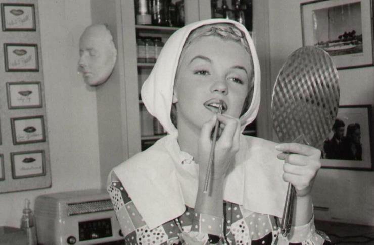 Marilyn Monroe applies lipstick while looking in a hand mirror.