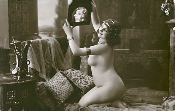 Vintage sepia-toned photograph, in which a nude woman kneels on a pillow-strewn bed, and holds a mirror over her head, while smiling. By Jean Agélou (1878-1921).