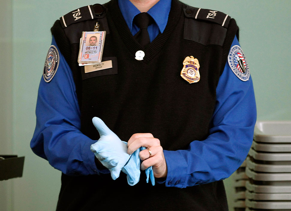 A uniformed TSA employee puts on the ominous light blue latex gloves.
