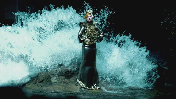 Still from 'Judas': Lady Gaga stands on a rock, wearing an elaborate gold gown, while enormous waves come crashing toward her from behind.