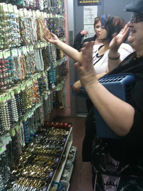 A handful of fats peruse a wall of a million shiny beaded necklaces.