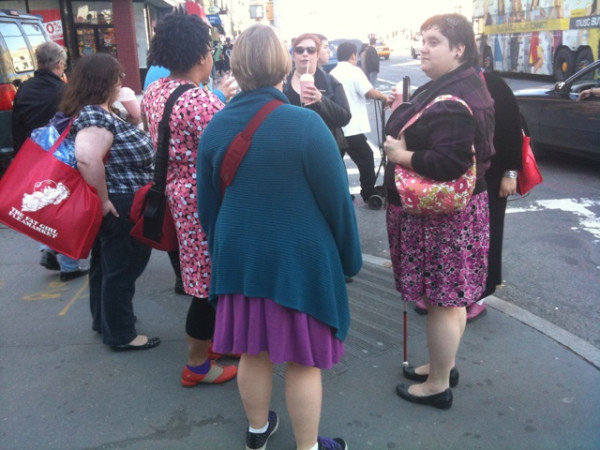 A collection of fats standing on a NY street corner waiting for the light to change.