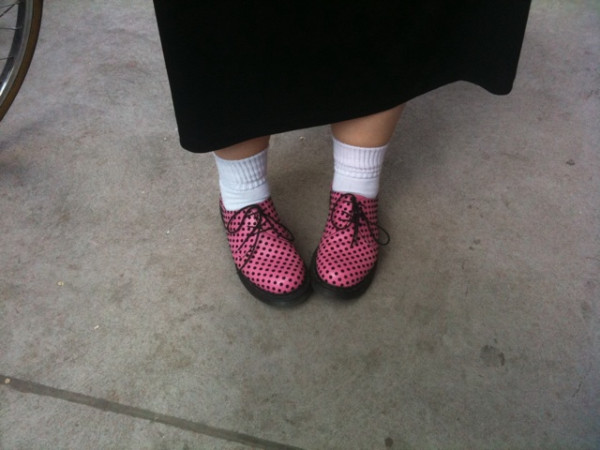 Image of Marianne's feet in white socks and pink and black polka-dotted Dr Martens oxfords, and the bottom of her long black dress.