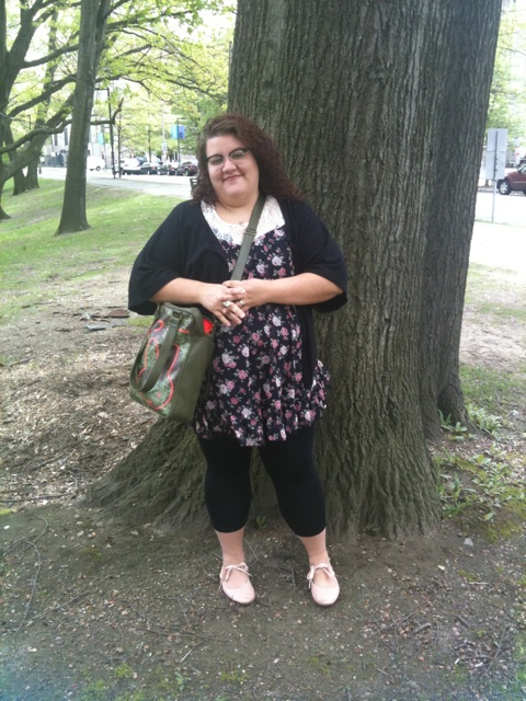 A photo of me, a fat white lady, standing outside next to a tree. I'm wearing a short black dress with small flowers on it, a black cardigan, black leggings, pink ballet-tie flats, and a dark green messenger bag. Also glasses. Also, I am smiling.