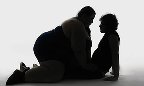 A very fat woman straddles a slender man, both in silhouetted profile.