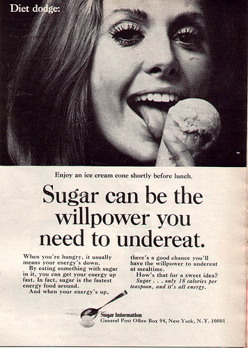 "1970s (?) ad for sugar, showing a woman licking an ice cream cone. Text reads: ""Enjoy an ice cream cone shortly before lunch. Sugar can be the willpower you need to undereat. When you're hungry, it usually means your energy's down. By eating something with sugar in it, you can get your energy up fast. In fact, sugar is the fastest energy food around. And when your energy's up, there's a good chance you'll have the willpower to undereat at mealtime. How's that for a sweet idea? Sugar... only 18 calories per teaspoon, and it's all energy."""